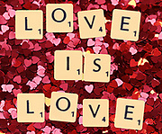 Digitally crated image of scrabble letters spelling LOVE IS LOVE on heart symbols background
