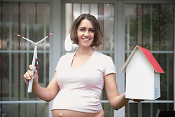 Pregnant woman holding model windmill model house
