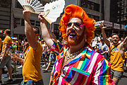 New York, NY - 30 June 2019. The New York City Heritage of Pride March filled Fifth Avenue for hours with participants from the LGBTQ community and it's supporters.A man in a brightly-striped shirt and orange hair.