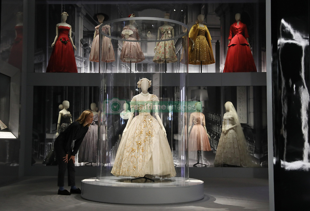 A gallery assistant looks at a dress during the preview into the 'Christian Dior: Designer of Dreams' exhibition held at the Victoria and Albert Museum, London. Picture dated: Wednesday January 30, 2019. Photo credit should read: Isabel Infantes / EMPICS Entertainment.