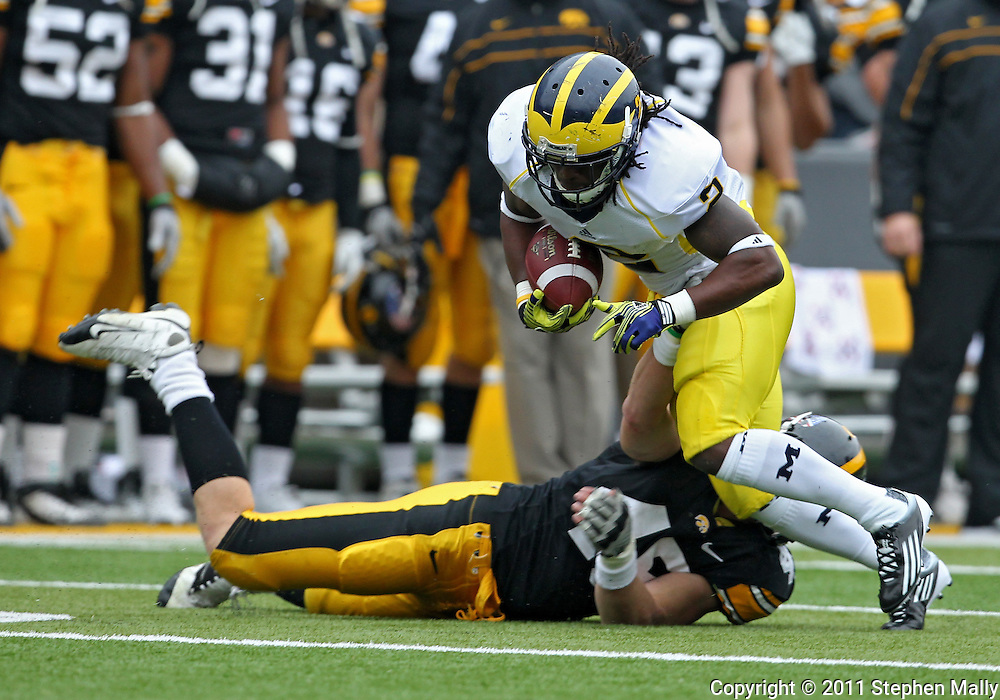 November 05, 2011: Michigan Wolverines running back Vincent Smith (2) tries to spin away from Iowa Hawkeyes linebacker Tyler Nielsen (45) during the second half of the NCAA football game between the Michigan Wolverines and the Iowa Hawkeyes at Kinnick Stadium in Iowa City, Iowa on Saturday, November 5, 2011. Iowa defeated Michigan 24-16.