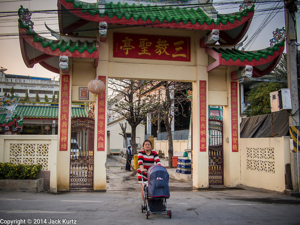 """25 JANUARY 2014 - BANG LUANG, NAKHON PATHOM, THAILAND: A performer with the Sing Tong Teochew opera troupe walks her baby across the street before a show in a Chinese shrine in the town of Bang Luang, Nakhon Pathom, Thailand. The Sing Tong Teochew opera troupe has been together for 60 years and travels through central Thailand and Bangkok performing for mostly ethnic Chinese audiences. Chinese opera was once very popular in Thailand, where it is called """"Ngiew."""" It is usually performed in the Teochew language. Millions of Chinese emigrated to Thailand (then Siam) in the 18th and 19th centuries and brought their cultural practices with them. Recently the popularity of ngiew has faded as people turn to performances of opera on DVD or movies. There are still as many 30 Chinese opera troupes left in Bangkok and its environs. They are especially busy during Chinese New Year when travel from Chinese temple to Chinese temple performing on stages they put up in streets near the temple, sometimes sleeping on hammocks they sling under their stage.     PHOTO BY JACK KURTZ"""