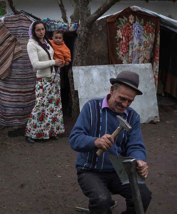 A Roma man makes a dustpan from scrap metal in a temporary camp in the village of  Dersca in Botosani County, Romania, while a young woman carrying her son on her hip watches him. They are Kelderari Roma, known for their skill in metal work, and their group has been permitted to set up camp in the farming village of Dersca, where they offer their services to the local inhabitants.