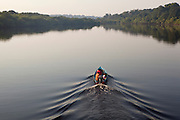 A family sails the Rio Negro on a boat on a quite morning, Amazonas, Brazil.