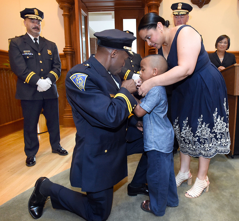 (Mara Lavitt — New Haven Register) <br /> July 1, 2014 New Haven<br /> A ceremony was held at New Haven City Hall to swear in two new New Haven assistant chiefs of police: Al Vazquez and Anthony Campbell, shown here getting his badge pinned on by son Paxon age 5 and wife Stephanie.<br /> mlavitt@newhavenregister.com