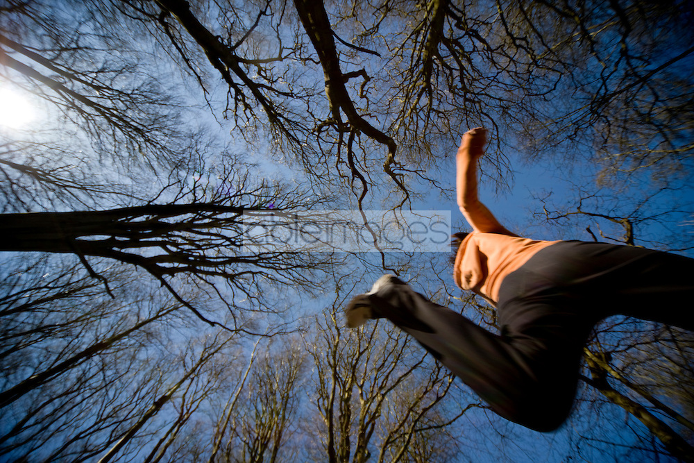 Woman jumping mid air with trees and blue sky