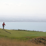 Golfers at Cape Kidnappers exclusive golf course. Hawkes  Bay, North Island, New Zealand..Completed in 2004 and designed by legendary golf architect Tom Doak,  Cape Kidnappers is a par 71 golf course measuring 7,119 yards (6,510 meters), the spectacular New Zealand golf course has been hailed as one of the great modern marvels in golf. Cape Kidnappers golf course is currently ranked the 41st best golf course in the world by Golf Magazine showing dramatic cliff top setting. Cape Kiddnappers, Hawkes Bay, New Zealand. 5th January 2011 Photo Tim Clayton