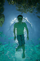A 13 year-old boy swimming in a pool.