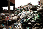 Heaps of garbage piled in a storage lot between two houses.