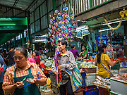 01 APRIL 2014 - BANGKOK, THAILAND:  A toy vendor walks through the Bangkok flower market. The Yodpiman Flower Market (also called Pak Khlong Talat) is being renovated and gentrified. The market opened in 1961 and has been a Bangkok landmark for more than 50 years, is being turned into a high end mall. Many of the flower and vegetable vendors in the market may be forced out.   PHOTO BY JACK KURTZ