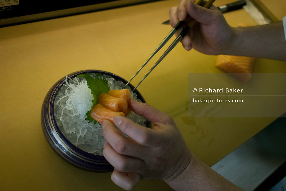 Detail of a chef's hands, preparing salmon with tongs in 'So', a sushi restaurant in central London.
