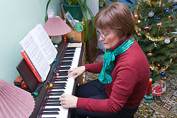 Woman; who has been undergoing Chemotherapy treatment for breast cancer; sitting playing her piano at home,