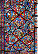 Medieval Windows  of the Gothic Cathedral of Chartres, France, dedicated to the life an miracles of St Nicholas. A UNESCO World Heritage Site. Bottom corners, left shows a belt seller, right a merchant. Centre panel, bottom shows a merchant with scales, left birth of St Nicholas, left the miracles of the first bath of St Nicholas, top The infant St Nicholas refuses his mother's milk except on mondays and fridays..Centre panel above ,  bottom shows The young St Nicholas does well at school, left Nicholas secretly gives gold to an old man to save his daughters , right The old man tries to thank Nicholas, who humbly flees from him, top Nicholas is chosen to be the new Bishop of Myra. .<br /> <br /> Visit our MEDIEVAL ART PHOTO COLLECTIONS for more   photos  to download or buy as prints https://funkystock.photoshelter.com/gallery-collection/Medieval-Middle-Ages-Art-Artefacts-Antiquities-Pictures-Images-of/C0000YpKXiAHnG2k
