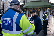 Protester discussing anti-vaccination opinions with police in the West End as the Prime Minister announces a new tighter fourth tier of local coronavirus restrictions for London and the South East, and that the planned Christmas relaxation of the rules was to be scrapped on 19th December 2020 in London, United Kingdom. Vaccine hesitancy, also known as anti-vaccination or anti-vax, is a reluctance or refusal to be vaccinated or to have ones children vaccinated against contagious diseases despite the availability of vaccination services.