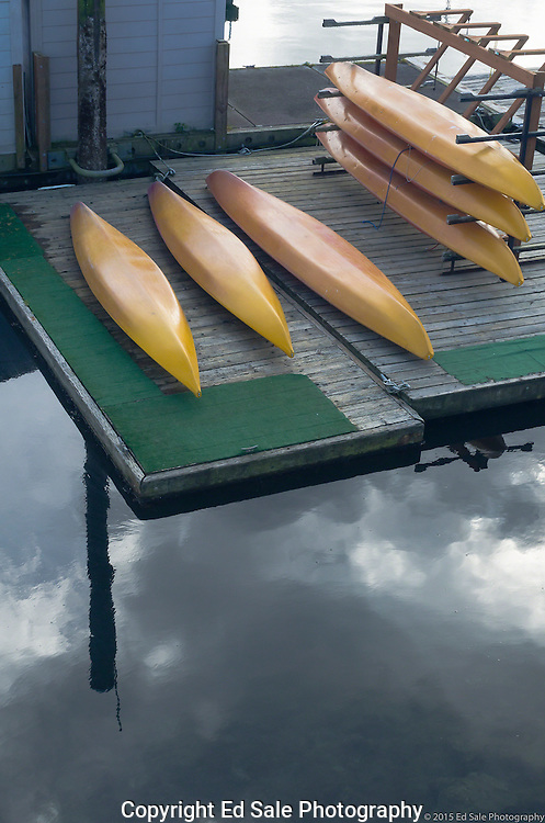 Yellow kayaks rest on dock in Port Ludlow, Washington during cloudy weather with storm clouds reflected in water