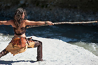 """Woman in tribal style practicing self defense with a longstick. Model: Elise Kost with Art Medicine Adornment <br /> :::<br /> """"We have this old technology for dealing with fear that helped us survive -- freeze, fight and flee. But stalking your fear is a quantum leap that helps change your relationship to fear. Choose instead the brave-hearted path of stalking, tracking, studying and allying with your fear.""""<br /> Ana Forrest"""