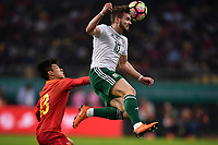 Tom Bradshaw, top, of Wales national football team heads the ball to make a pass against He Chao of Chinese national men's football team in the semi-final match during the 2018 Gree China Cup International Football Championship in Nanning city, south China's Guangxi Zhuang Autonomous Region, 22 March 2018.