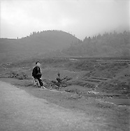 A young shepherd boy sits on the side of the road, near Sapa, Vietnam.2005