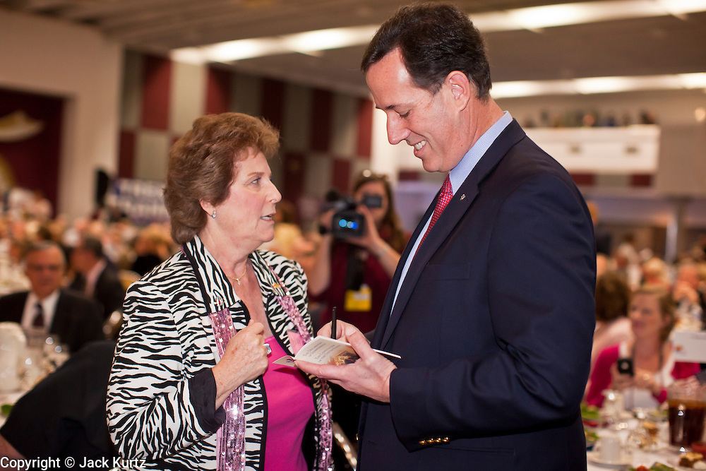 """21 FEBRUARY 2012 - PHOENIX, AZ:  Former US Senator and Republican Presidential candidate RICK SANTORUM signs a copy of the """"Declaration of Independence"""" for a supporter at the Maricopa County Lincoln Day lunch in Phoenix. Santorum was in Phoenix Tuesday for an Arizona Republican party leadership luncheon ahead of the state's Republican Presidential Primary election and a CNN Republican Presidential Primary debate, which is Wednesday, Feb. 22.    PHOTO BY JACK KURTZ"""