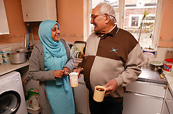 Asian carer with elderly Asian man in the kitchen chatting and making tea, ***NOT TO BE USED IN THE EAST MIDLANDS***