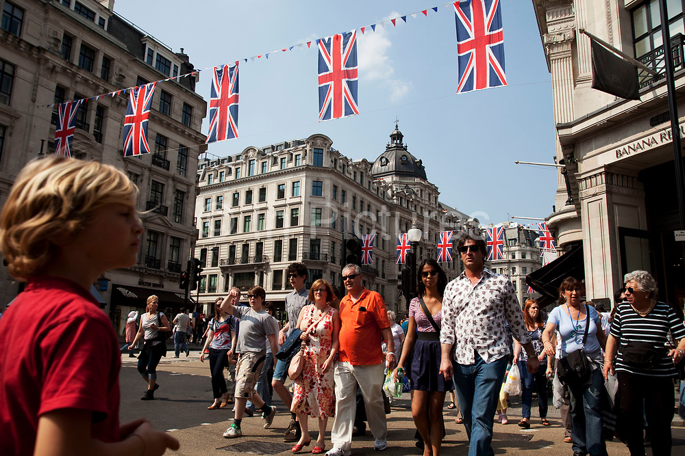 People cross the busy shopping street under Royal Wedding Union flags on Regent Street, London. A display of 200 giant Union Jack Flags run all the way along from Piccadilly Circus to beyond Oxford Circus. Each flag is 4 x 2.5 metres in size and hang from 22 crossings to celebrate the Royal Wedding, recreating a majestic architectural view of one of the world's most famous historical shopping thoroughfares.