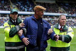A Bristol Rovers fan gets escorted off the pitch after invading the pitch - Photo mandatory by-line: Dougie Allward/JMP - Mobile: 07966 386802 26/04/2014 - SPORT - FOOTBALL - High Wycombe - Adams Park - Wycombe Wanderers v Bristol Rovers - Sky Bet League Two