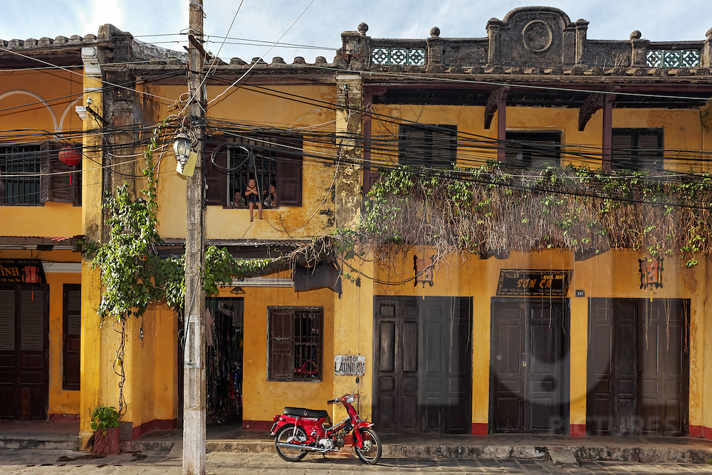 Bright red motorbike sits outside a French colonial building in Hoi An, Vietnam, Southeast Asia. A little boy can be seen in an upstairs window hanging through the bars.