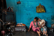 Poonam, 13, (left) and her oldest sister Arti, 19, having a cup of Indian chai tea, are relaxing on the floor of their newly built home in Oriya Basti, one of the water-contaminated colonies in Bhopal, central India, near the abandoned Union Carbide (now DOW Chemical) industrial complex, site of the infamous '1984 Gas Disaster'.