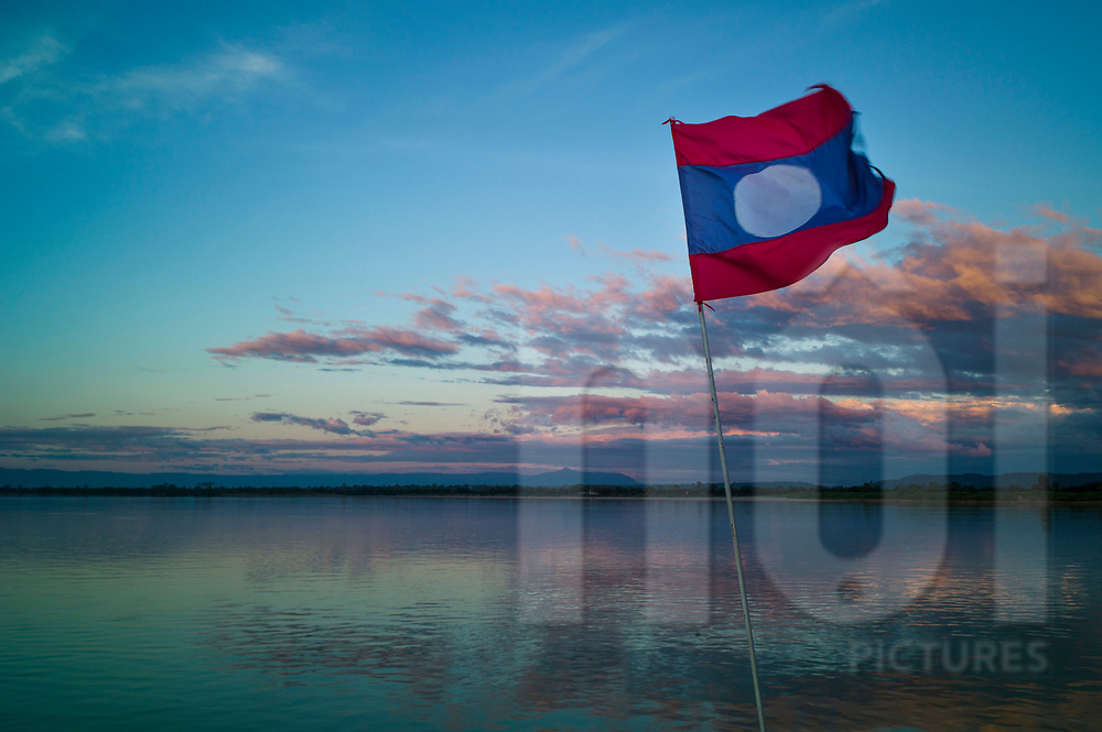 Laos flag floats on a cruising boat sailing the Mekong river in Champassak Province, Laos, Southeast Asia