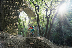Man riding bike over footpath by arched stone wall in forest