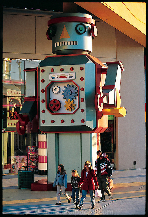 Passersby amble past the friendly robot giant at the doorway of FAO Schwarz in Orlando, Florida. From the book Robo sapiens: Evolution of a New Species, page 1.