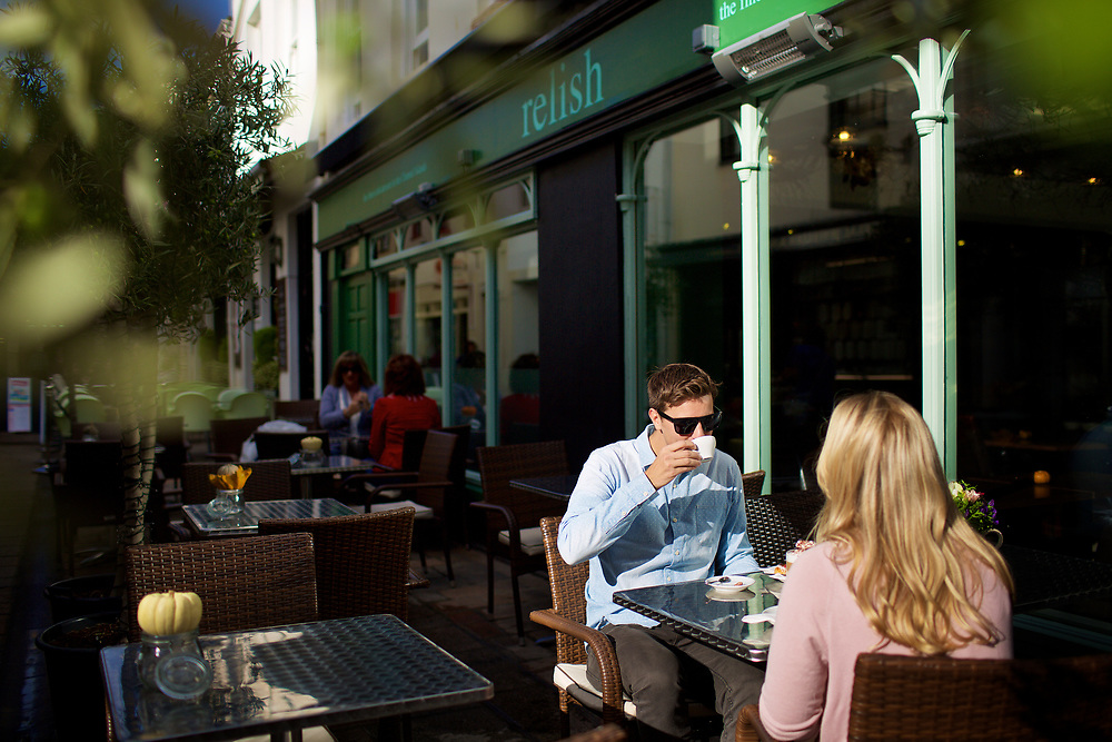 People socialising, eating and drinking outside the delicatessen and cafe Relish in St Helier town centre, Jersey, CI