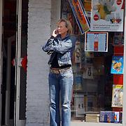 NLD/Laren/20050510 - Marleen Houter voor kledingwinkel  bellend met mobiele telefoon op straat