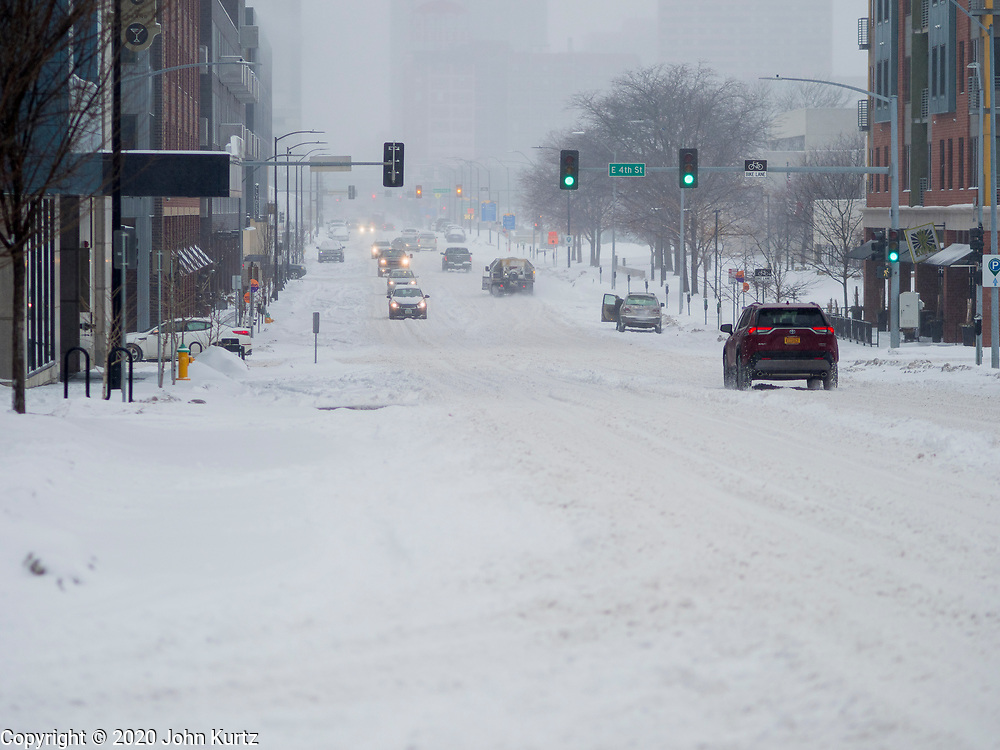 17 JANUARY 2020 - DES MOINES, IOWA: Traffic on snow packed Grand Ave. in the East Village neighborhood of Des Moines Friday afternoon. The second significant snow fall in a week hit central Iowa Friday. The snow started falling during the morning rush hour and by early afternoon about five inches had fallen in Des Moines. Meteorologists said up to 1/10 of an inch of ice could cover the snow by the end of the day. The snowstorm was expected to turn into a blizzard in northern Iowa on Saturday with wind speeds above 30MPH. Many businesses in the Des Moines area closed early Friday and several of the Democratic presidential candidates cancelled their campaign events because of the snow.    PHOTO BY JACK KURTZ