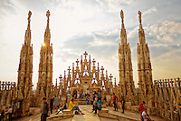 View of spires and tourists on the Duomo Cathedral at sunset, Milan Italy