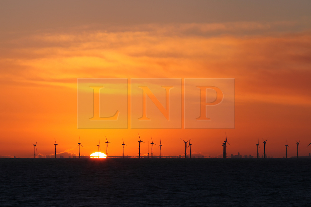 © Licensed to London News Pictures. 22/03/2014. North Wales, UK. The sun rises over the North Hoyle Offshore Wind Farm off the coast of North Wales this morning, 22nd March 2014. The Liverpool skyline can be seen on the horizon. Photo credit : Rob Arnold/LNP