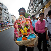 A young man carries his idol of Lord Ganesh on his way to immerse it in the Indian ocean on the last day of the Ganesh Chaturthi festival. Ganesh, the elephant-headed son of Shiva and Parvati is widely worshiped as the supreme God of wisdom, prosperity and good fortune. Mumbai, September 2009.
