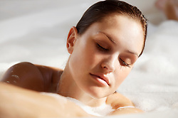 Close up of a young woman face in a bubble bath