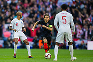 Luka Modrić (Capt) (Croatia) controls the ball with Fabian Delphi (England) on the inside and heading in the path of Joe Gomez (England) during the UEFA Nations League match between England and Croatia at Wembley Stadium, London, England on 18 November 2018.
