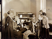 Six National Woman's Party members gathered around a desk at National Woman's Party headquarters. Left to right: Mabel Vernon, Dora Lewis, Alice Paul (seated), Florence Brewer Boeckel, Abby Scott Baker, and Anita Pollitzer. February 1921.