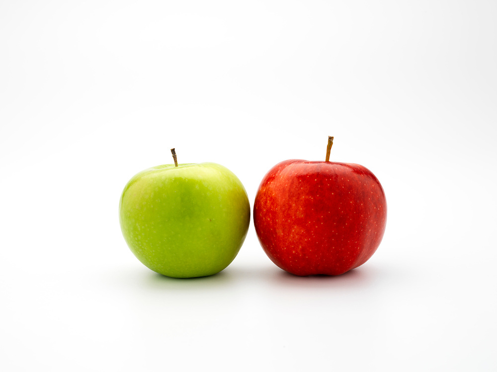 Red and a green apple on a white background