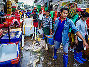 23 NOVEMBER 2017 - YANGON, MYANMAR: Workers carry a basket of river prawns to a truck in the San Pya Fish Market. San Pya Fish Market is one of the largest fish markets in Yangon. It's a 24 hour market, but busiest early in the morning. Most of the fish in the market is wild caught but aquaculture is expanding in Myanmar and more farmed fresh water fish is being sold now than in the past.    PHOTO BY JACK KURTZ