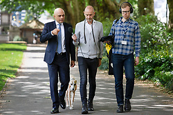 © Licensed to London News Pictures. 17/06/2019. London, UK. Home Secretary and Conservative Party Leadership contender Sajid Javid is interviewed by BBC Radio 4 presenter Evan Davis in Victoria Tower Gardens. They are followed closely by Evan's dog Mr Whippy. Photo credit: George Cracknell Wright/LNP