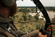 Hughes 500 helicopter & Barney O'Hara<br /> to dart Buffalo (Syncerus caffer)<br /> Gorongosa National Park<br /> Mozambique, Africa<br /> Buffalo to be darted from helicopter for blood and Probang (throat scrape) samples to test for foot-and-mouth disease to prepare localized vaccines for regionally different foot-and-mouth strains.