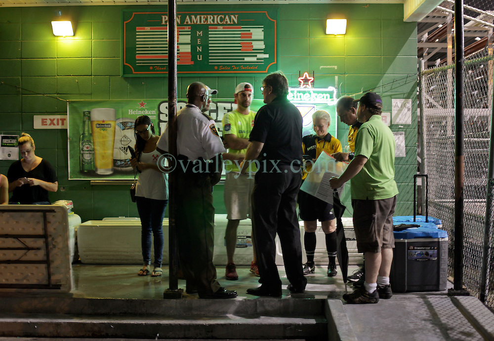 04 June 2016. New Orleans, Louisiana.<br /> NPSL Soccer, Pan American Stadium.<br /> New Orleans Jesters v Birmingham Hammers. Jesters win 4-1 when lightning stopped play in the 66th minute of the game. Referees and coaches consult the rules as the game is called.<br /> Photo; Charlie Varley/varleypix.com