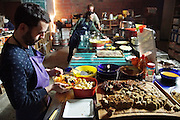 """Volunteer cooks in preparation of the banana cake and fruit dessert.<br /><br />The Freegan Pony is an alternative restaurant housed in a squat. It was founded in 2015 by Aladdin Charni with three other collaborators. The restaurant specialises in cheap vegetarian cuisine, serving meals which guests reserve a place through a Facebook group, paying €2 a meal. The restaurant meals contain unsold and donated food, collected from wholesellers at the Paris Rungis vegetable market. The Freegan Pony is located at the Porte de la Vilette on the outskirts of Paris, at the entrance to the peripherique outer circle motorway.<br /><br />Freegans are people who employ alternative strategies for living based on limited participation in the conventional economy and minimal consumption of resources. Freeganism is the practice of reclaiming and eating food that has been discarded. People who attempt to live an ethical lifestyle by reusing trash and rubbish thrown away by others.<br /><br />Freeganism is an ill-defined activity and is a subset of the larger anti-capitalist and environmental protest movements. It embraces alternative, anti-consumerist lifestyles. Freegan practices also include co-operative living, squatting and """"freecyling"""", or matching things that people want to get rid of with things other people need"""