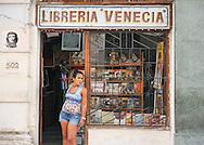 Woman standing in the door of a bookstore<br /> Havana, Cuba, 2015