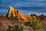 An orange sunrise lights rock formations near Ben Reifel Visitor Center in Badlands National Park, South Dakota, USA. The intricately carved cliff of the Badlands Wall constantly retreats as it erodes and washes into the White River Valley below.