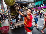 """18 MAY 2017 - BANGKOK, THAILAND: A worker delivers durian to a street food stall on Yaowarat Road in Bangkok. City officials in Bangkok have taken steps to rein in street food vendors. The steps were originally reported as a """"ban"""" on street food, but after an uproar in local and international news outlets, city officials said street food vendors wouldn't be banned but would be regulated, undergo health inspections and be restricted to certain hours on major streets. On Yaowarat Road, in the heart of Bangkok's touristy Chinatown, the city has closed some traffic lanes to facilitate the vendors. But in other parts of the city, the vendors have been moved off of major streets and sidewalks.      PHOTO BY JACK KURTZ"""
