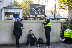 London, UK. 13 October, 2019. Metropolitan Police officers detain a man during a protest by disabled climate activists from Extinction Rebellion outside New Scotland Yard.